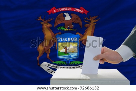 man putting ballot in a box during elections  in front of flag american state of michigan
