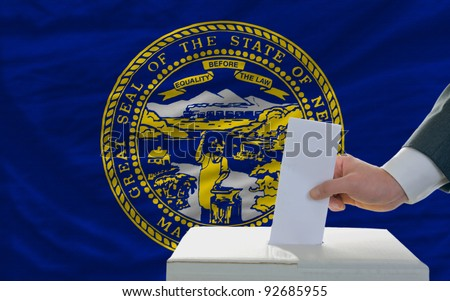 man putting ballot in a box during elections  in front of flag american state of nebraska