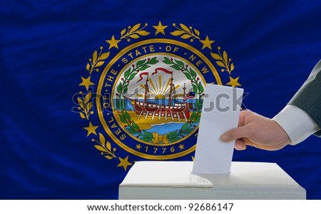 man putting ballot in a box during elections  in front of flag american state of new hampshire