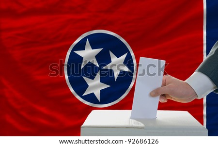 man putting ballot in a box during elections  in front of flag american state of tennessee - stock photo