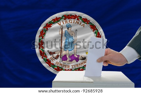 man putting ballot in a box during elections  in front of flag american state of virginia