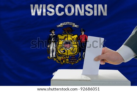 man putting ballot in a box during elections  in front of flag american state of wisconsin