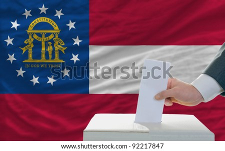 man putting ballot in a box during elections in georgia in front of flag