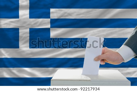 man putting ballot in a box during elections in greece in front of flag