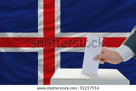 man putting ballot in a box during elections in iceland in front of flag