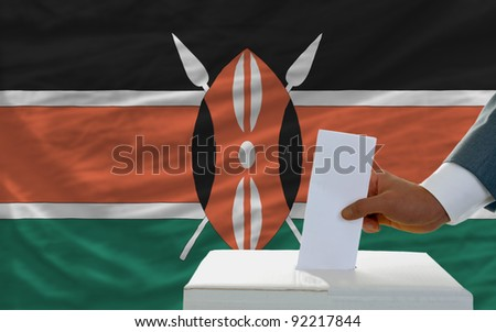 man putting ballot in a box during elections in kenya in front of flag