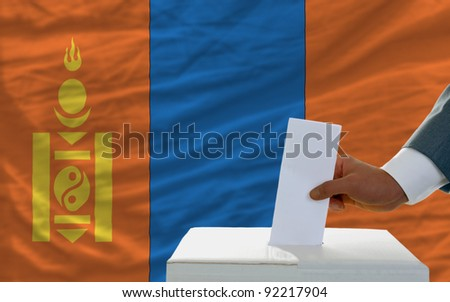 man putting ballot in a box during elections in mongolia in front of flag