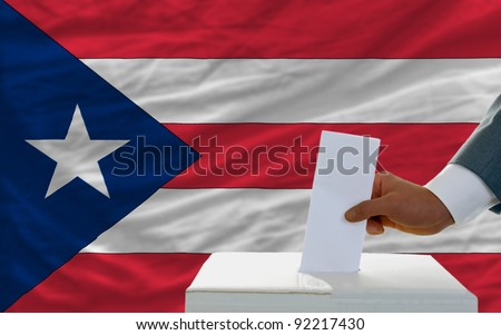 man putting ballot in a box during elections in puerto rico in front of flag - stock photo