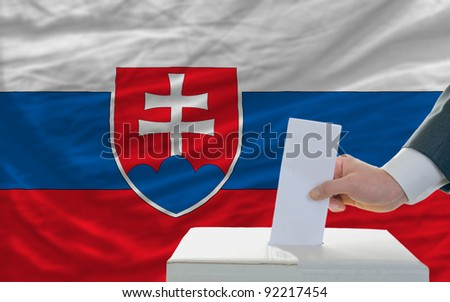 man putting ballot in a box during elections in slovakia in front of flag