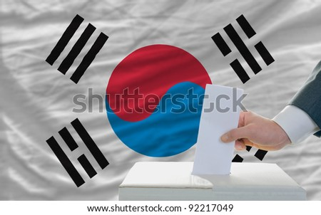 man putting ballot in a box during elections in south korea in front of flag