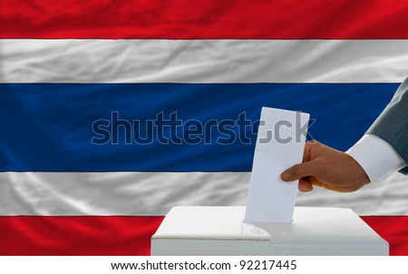 man putting ballot in a box during elections in sri lanka in front of flag
