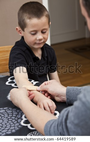 Man putting Band-Aid on sons arm