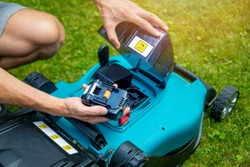 man putting battery into electric cordless lawn mower