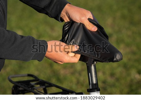Man putting black rain cover on the bicycle saddle. Bicycle waterproof seat cover. Bike seat care stock photo