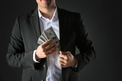 Man putting bribe money into pocket on black background, closeup
