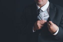 Man putting bribe money into pocket on black background, Concept for corruption, finance profit, bail and crime
