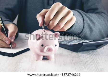 Man putting coin in piggy bank. #1373746211