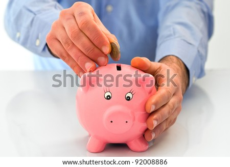 Man putting coin into a piggy bank.