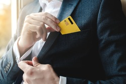 Man putting credit card in suit pocket