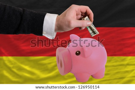 Man putting dollar into piggy rich bank national flag of germany in foreign currency because of inflation