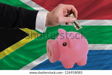 Man putting dollar into piggy rich bank national flag of south africa in foreign currency because of inflation