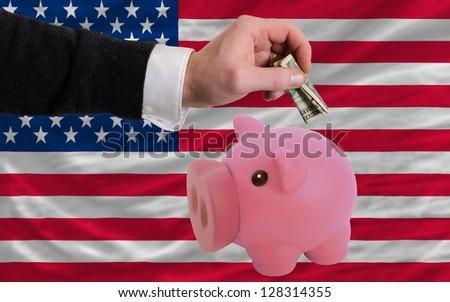 Man putting dollar into piggy rich bank national flag of us in foreign currency because of inflation
