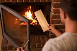 Man putting dry firewood into fireplace at home, closeup. Winter vacation