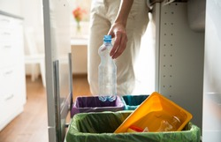 Man putting empty plastic bottle in recycling bin in the kitchen. Person in the house kitchen separating waste. Different trash can with colorful garbage bags.