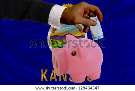 Man putting euro into piggy rich bank and flag of us state of kansas in foreign currency because of insecurity and inflation