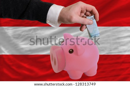 Man putting euro into piggy rich bank and national flag of austria in foreign currency because of insecurity and inflation