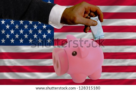 Man putting euro into piggy rich bank and national flag of us in foreign currency because of insecurity and inflation
