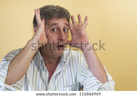 man putting his hands to his head