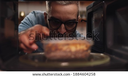 Man putting leftover dinner into microwave oven to cook. View from inside microwave of guy putting dinner in plastic container to warm. Male heating meal in oven