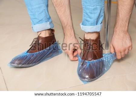 Man putting on blue shoe covers, closeup #1194705547