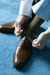 Man putting on brown leather shoes for work