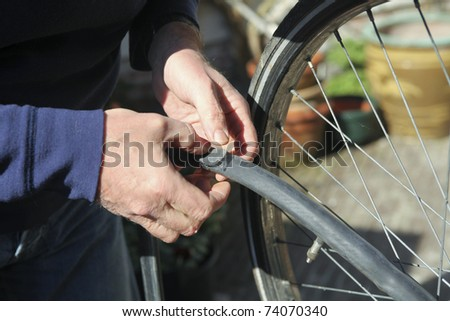 Man putting rubber band on flat bike tire