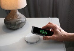 Man putting smartphone on wireless charger in room, closeup