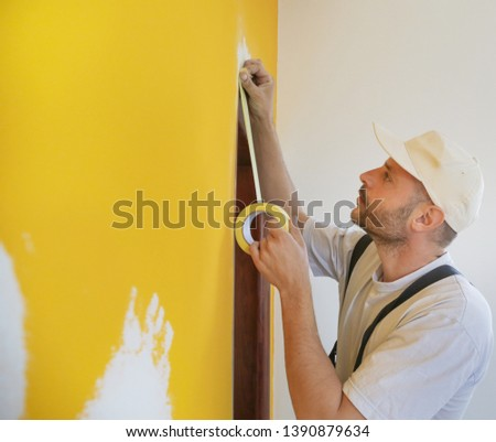 Man putting tape on the wall. The simple step for the quick and easy painting process. Renovation house concept. Foto stock ©