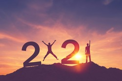Man raise hand up and man jumping on sunset sky at top of mountain and number like 2021 abstract background. Happy new year and holiday celebration concept. Vintage tone filter effect color style.