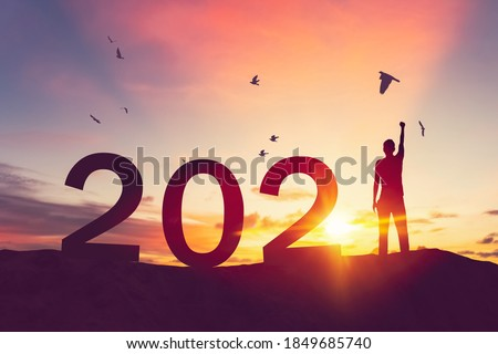 Man raise hand up on sunset sky with birds flying at top of mountain and number like 2021 abstract background. Happy new year and holiday concept. Vintage tone filter effect color style.