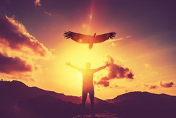 Man raise hand up on top of mountain and sunset sky star with eagle bird fly abstract background. Copy space freedom travel adventure and business victory concept. Vintage tone filter effect color.