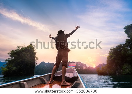 Man raised hands enjoying to adventure trip of a lifetime floating in a boat on the asia lake with sunset among the islands with mountains  #552006730