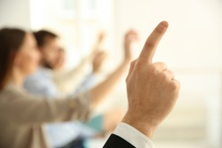 Man raising hand to ask question at business training indoors, closeup