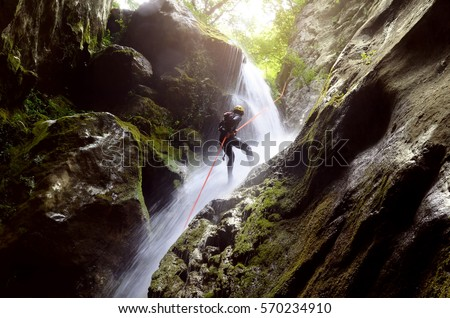 man rappelling down a waterfall backlit  Photo stock ©