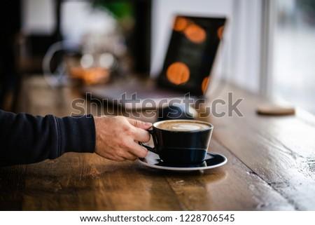 MAN REACHING FOR COFFEE LATTE #1228706545