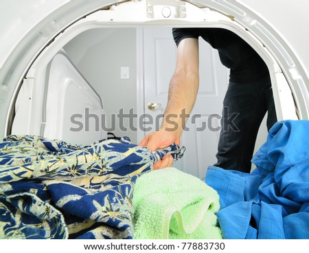 Man reaching into a dryer to pull out laundry.