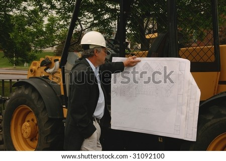 man reading a blueprint on a piece of construction equipment