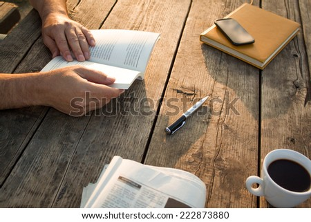 Man reading a book and writing notes on wooden table on sunset.