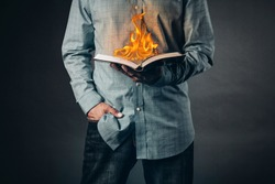 Man reading a book on fire. Reading concept.