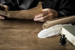Man reading an old letter. Old quill pen, book and papyrus scroll on the wooden table. Historical atmosphere.
